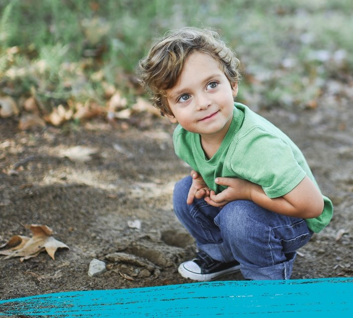 A child wearing a green t-shirt playing in the Australian bush.
