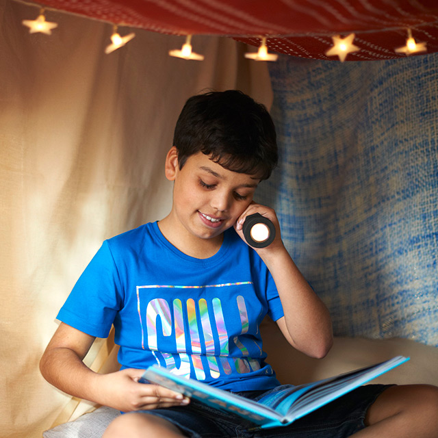 Boy reading book with torch