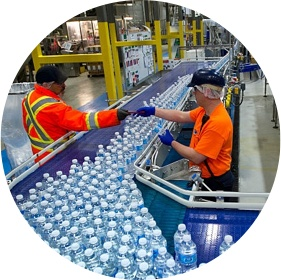 workers inspecting water bottles on production line